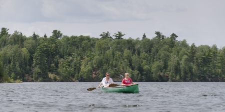 Two girls rowing a boat in a lake, Lake of The Woods, Ontario, Canada