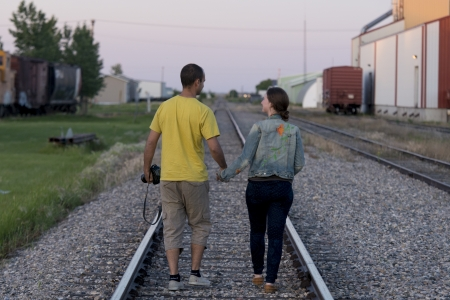 Couple walking between railroad tracks, Manitoba, Canada