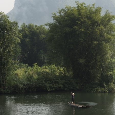 placidness: Man on raft on the Yulong River, Yangshuo, Guilin, Guangxi Province, China Stock Photo