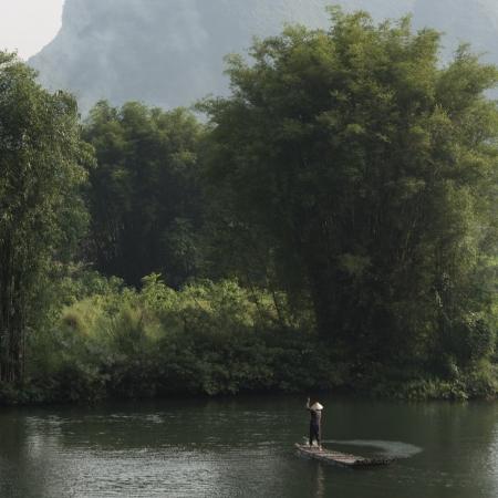 Man on raft on the Yulong River, Yangshuo, Guilin, Guangxi Province, China 版權商用圖片