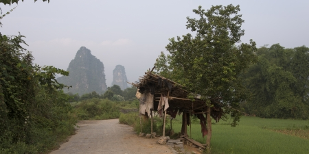 placidness: Dirt road passing through fields, Yangshuo, Guilin, Guangxi Province, China Stock Photo