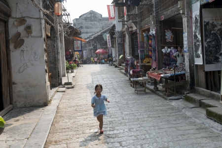 Little girl walking on a street, Xingping, Yangshuo, Guilin, Guangxi Province, China