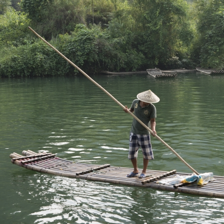 placidness: Man on raft in the Yulong River, Yangshuo, Guilin, Guangxi Province, China Stock Photo