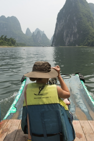 placidness: Tourist on a raft in Li River, Yangshuo, Guilin, Guangxi Province, China