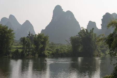 Person on raft in the Yulong River, Yangshuo, Guilin, Guangxi Province, China