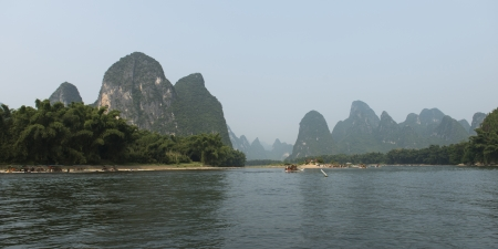 placidness: Tourboats in the Li River with mountains in the background, Yangshuo, Guilin, Guangxi Province, China Stock Photo