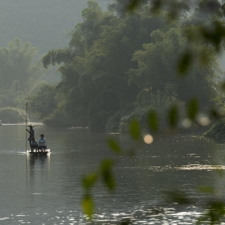 Tourists on a bamboo raft in Yulong River, Yangshuo, Guilin, Guangxi Province, China