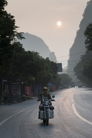 freetime activity: Man riding a motorcycle on the road, Yangshuo, Guilin, Guangxi Province, China