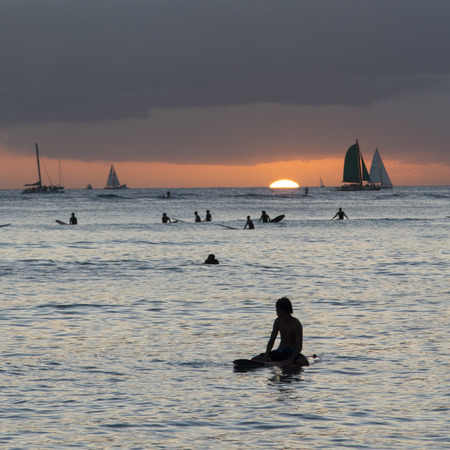 honolulu: People surfing in the ocean at sunset, Waikiki, Honolulu, Oahu, Hawaii, USA Editorial
