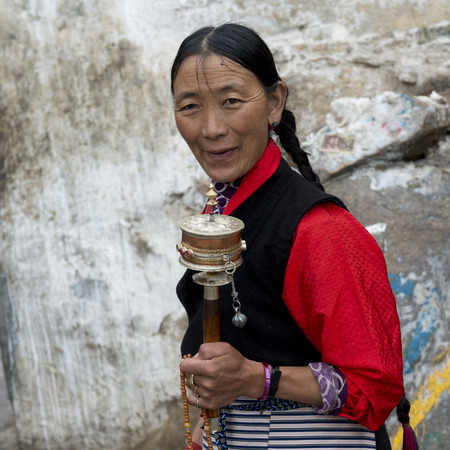Buddhist woman with prayer wheel in Drepung Monastery, Lhasa, Tibet, China