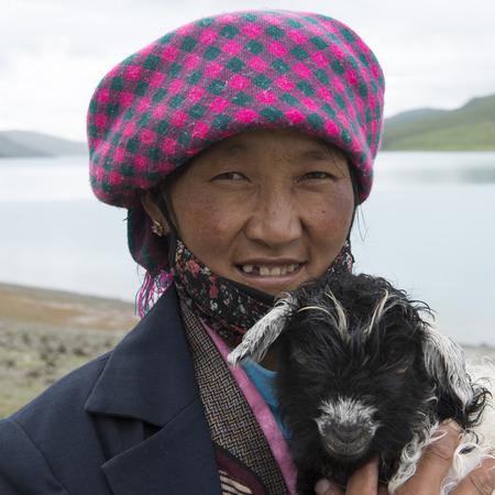 Woman holding a lamb at the lakeside, Yamdrok Lake, Tibet, China