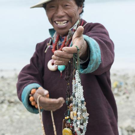 satisfies: Tibetan man selling beaded necklaces, Nagarze, Shannan, Tibet, China