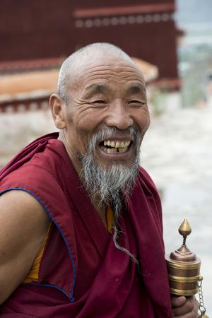 satisfies: Buddhist monk with prayer wheel in Drepung Monastery, Lhasa, Tibet, China Editorial