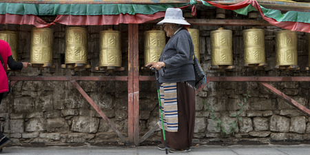 Pilgrim spinning prayer wheels at Potala Palace, Lhasa, Tibet, China