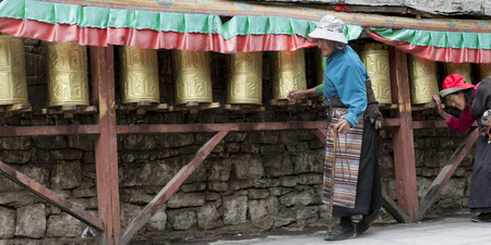 Pilgrims spinning prayer wheels at Potala Palace, Lhasa, Tibet, China