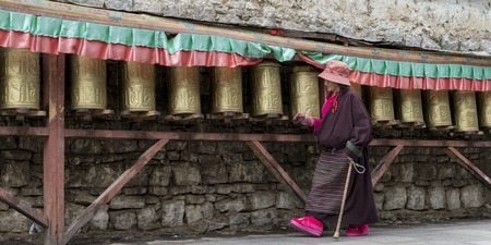 potala: Pilgrim spinning prayer wheels at Potala Palace, Lhasa, Tibet, China Editorial