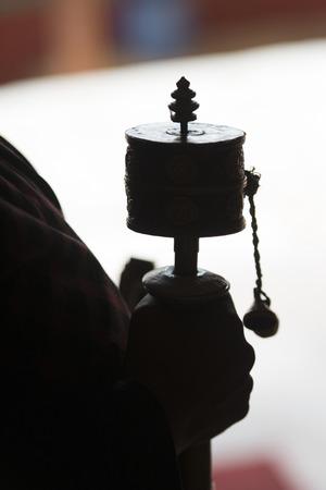 Buddhist pilgrim with prayer wheel in Drepung Monastery, Lhasa, Tibet, China