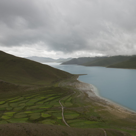 Aerial view of road passing through agricultural fields along Yamdrok Lake, Nagarze, Shannan, Tibet, China photo