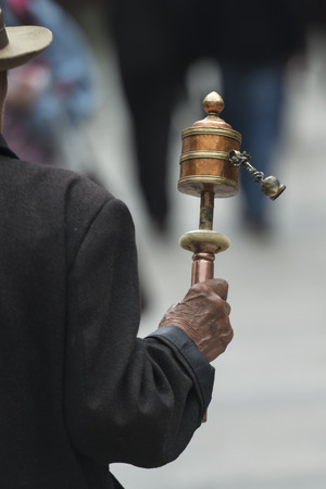 Buddhist pilgrim with prayer wheel on a street, Lhasa, Tibet, China photo