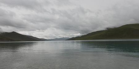 Yamdrok Lake with mountains under cloudy sky, Nagarze, Shannan, Tibet, China photo