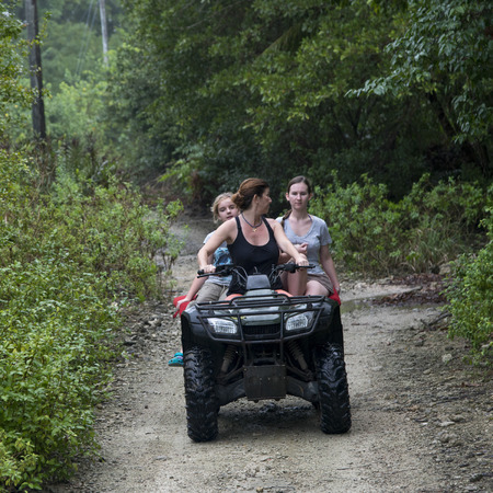 recreational vehicle: Woman riding quadbike with her teenage daughters on dirt road, Utila, Bay Islands, Honduras
