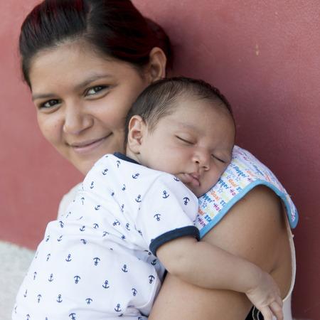 Closeup of a woman holding her baby, Copan, Copan Ruinas, Honduras 写真素材