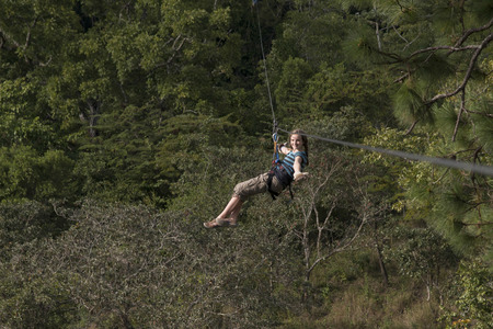 Girl riding a zip line in a forest, Copan, Copan Ruinas, Copan Department, Honduras