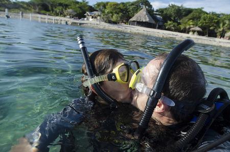 utopia: Couple kissing with scuba gears in the sea, Utopia Village, Utila, Bay Islands, Honduras