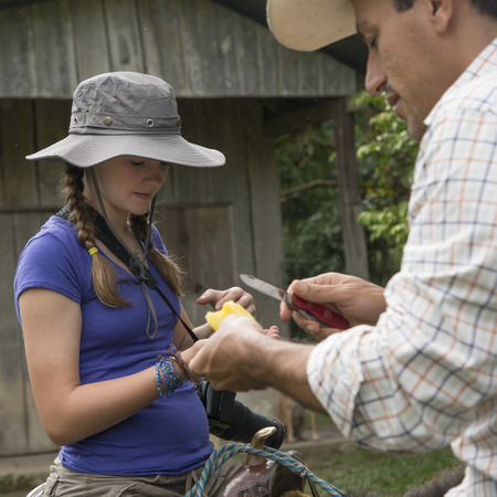 food photography: Man giving slice of fruit to a teenage girl, Finca El Cisne, Honduras Editorial