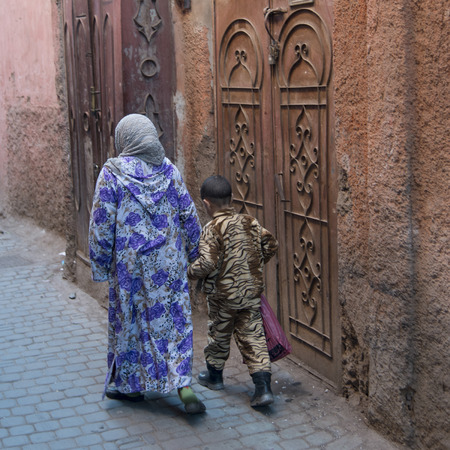 africa child: Woman with her son walking on a street, Medina, Marrakesh, Morocco Stock Photo
