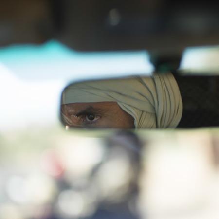 Reflection of a Tuareg man in the rear-view mirror, Atlas Mountains, Morocco