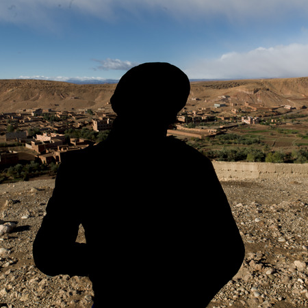 waistup: Tuareg man looking at a town view from the terrace of a fort, Ait Benhaddou, Ouarzazate, Souss-Massa-Draa, Morocco Stock Photo