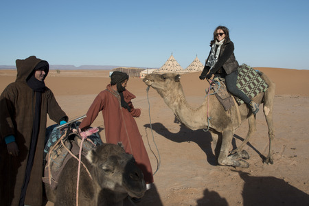 People with camels in a desert, Erg Chigaga Luxury Desert Camp, Sahara Desert, Souss-Massa-Draa, Morocco photo