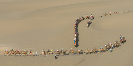 Tourists riding camels at Mingsha Shan, Dunhuang, Jiuquan, Gansu Province, China 免版税图像
