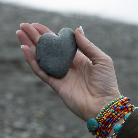 tough woman: Close-up of a womans hand holding a heart shaped stone, Deception Pass State Park, Oak Harbor, Washington State, USA
