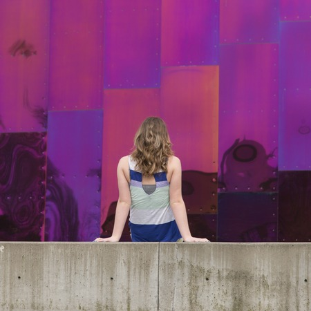 Back view of teenage girl in front of EMP Museum exterior, Seattle, Washington State, USA 版權商用圖片