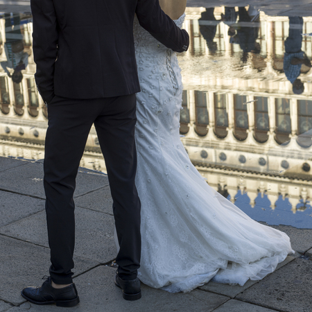 vecchie: Low section of bride and groom walking on sidewalk, Procuratie Vecchie, St Marks Square, Venice, Veneto, Italy
