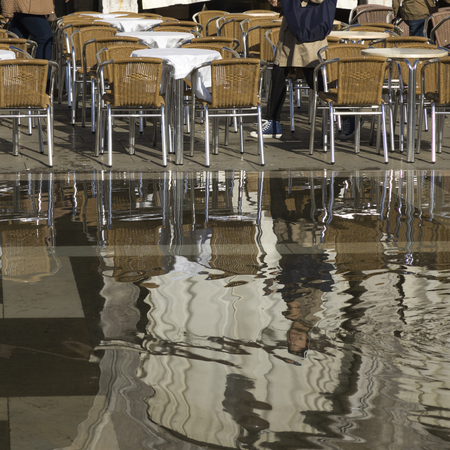 incidental people: Chairs and tables at sidewalk cafe on wet street, St Marks Square, Venice, Veneto, Italy