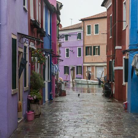 incidental people: View of houses along wet street, Burano, Venice, Veneto, Italy