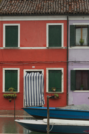 canal house: Boats moored at canal by house, Burano, Venice, Veneto, Italy Stock Photo