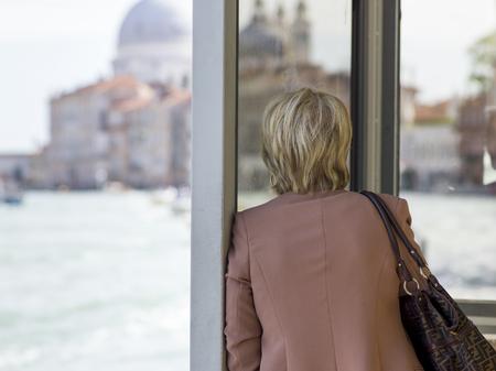 waistup: Back view of a woman looking through window at Santa Maria Della Salute by Grand Canal, Venice, Veneto, Italy Stock Photo