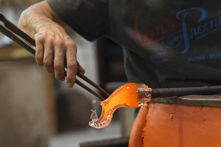 pinzas: Hombre que trabaja con vidrio fundido usando unas pinzas en la fábrica de cristal, Murano, Venecia, Véneto, Italia Foto de archivo