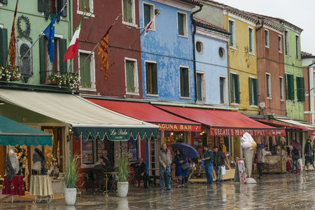 People outside of stores by wet street during rain, Burano, Venice, Veneto, Italy Redactioneel