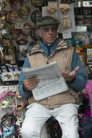 the merchant of venice: Man sitting at souvenir shop reading a newspaper, Venice, Veneto, Italy Editorial