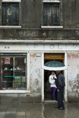 entranceway: People talking to each other at doorway during rain, Burano, Venice, Veneto, Italy Editorial