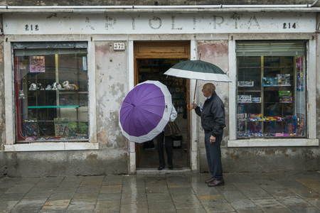 only two people: People standing at doorway of a shop during rain, Burano, Venice, Veneto, Italy