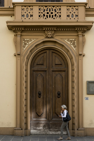 entranceway: Woman walking in front of doorway of building, Florence, Tuscany, Italy