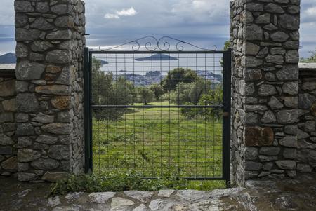 entranceway: Metal gate at park, Skiathos, Sporades, Greece Stock Photo
