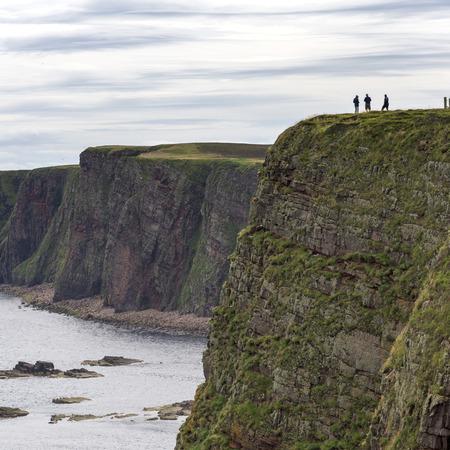 headland: Tourists on headland at coast, Duncansby Head, Caithness, Scottish Highlands, Scotland Stock Photo