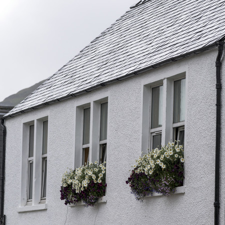 scottish culture: Low angle view of a house with flower boxes, Portree, Isle of Skye, Scottish Highlands, Scotland Stock Photo